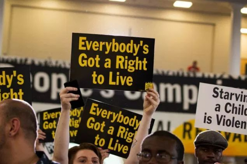 Attendees hold signs at the Poor People's Moral Action Congress at Trinity University in Washington D.C.