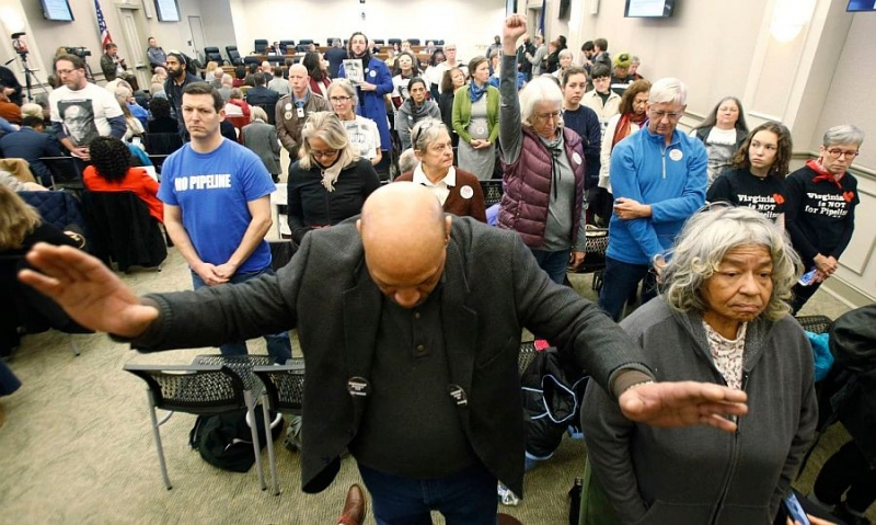 Richard Walker, an Atlantic Coast Pipeline opponent, raises his hands as he and other pipeline opponents turn their backs on a Dec. 19 meeting of a Virginia air pollution panel, which delayed a vote on a key permit for the Atlantic Coast Pipeline.